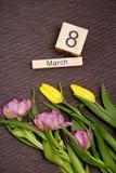 La inscripción el 8 de marzo con las flores en un fondo gris Foto de archivo