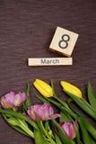La inscripción el 8 de marzo con las flores en un fondo gris Imagenes de archivo