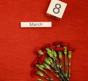 La inscripción el 8 de marzo con las flores en un fondo rojo Imagen de archivo