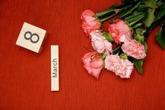 La inscripción el 8 de marzo con las flores en un fondo rojo Fotos de archivo
