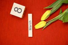 La inscripción el 8 de marzo con las flores en un fondo rojo Foto de archivo libre de regalías