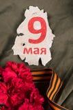 La inscripción el 9 de mayo en un pedazo del papel y de una cinta anaranjada Imagen de archivo libre de regalías