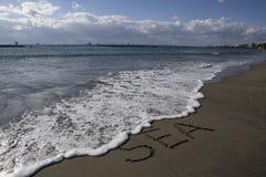La inscripción en arena de mar por el mar Imagen de archivo