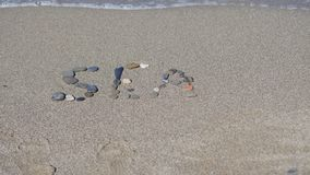 La inscripción en la arena del mar Imagen de archivo