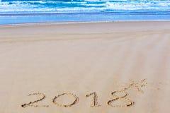 la inscripción 2018 en la arena y el mar mojados de la playa agita en fondo Fotografía de archivo libre de regalías