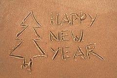 La inscripción en la Feliz Año Nuevo y el árbol de navidad de la arena Imagenes de archivo
