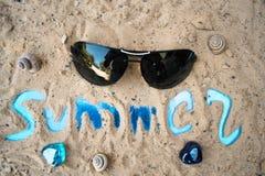 La inscripción en la arena de la playa soleada del verano Imagenes de archivo