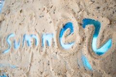 La inscripción en la arena de la playa soleada del verano Foto de archivo libre de regalías