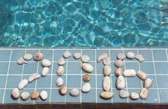 La inscripción 2016 es presentada por el guijarro en un lado de la piscina Imagen de archivo libre de regalías