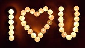La inscripción TE AMO hizo quemando velas en el fondo de madera Concepto del día del ` s de la tarjeta del día de San Valentín