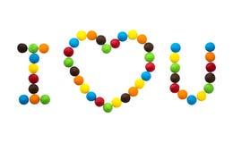 La inscripción te amo y el corazón de caramelos redondos multicolores Imágenes de archivo libres de regalías