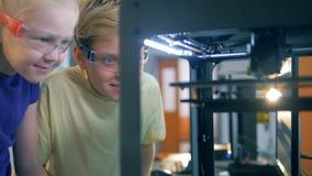 La instalación de Quantorium con una impresora 3D se sostuvo en ella y dos niños que la miraban en el trabajo almacen de metraje de vídeo