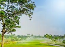 La irrigación asperja el sistema que riega en campo de golf foto de archivo libre de regalías