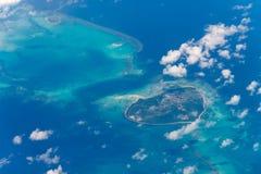 La isla del atolón en el océano azul a través de las nubes y del cielo azul marino Imagenes de archivo