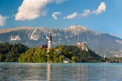 La isla en el lago sangró en un día soleado, Eslovenia Imagenes de archivo