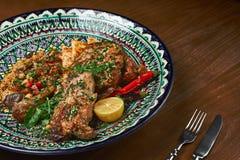 La jambe de l'agneau a fait cuire au four avec de la sauce dans un plat en céramique, plan rapproché avec un houmous garnissent C Image libre de droits