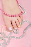 La jambe de la femme avec la belle pédicurie et les colliers colorés Images stock