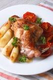 La jambe de lapin a rôti avec des pommes et des tomates sur un plan rapproché de plat Photographie stock libre de droits