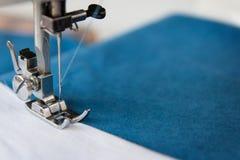 La jambe de la machine à coudre avec une aiguille coud le tissu bleu photo libre de droits