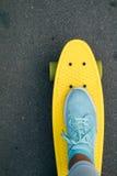 La jambe des femmes dans les blues-jean et des espadrilles se tenant sur le skateb jaune Photographie stock libre de droits