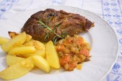 La jambe lentement rôtie d'agneau de ressort avec le romarin et l'ail a servi aux oignons vitrés par bonbon, carottes, pommes et  Photographie stock libre de droits
