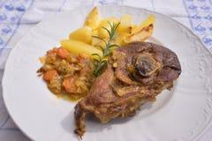 La jambe lentement rôtie d'agneau de ressort avec le romarin et l'ail a servi aux oignons vitrés par bonbon, carottes, pommes et  Photographie stock
