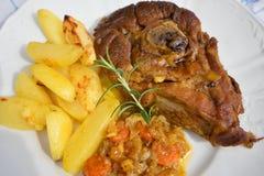 La jambe lentement rôtie d'agneau de ressort avec le romarin et l'ail a servi aux oignons vitrés par bonbon, carottes, pommes et  Photo libre de droits