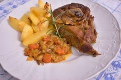 La jambe lentement rôtie d'agneau de ressort avec le romarin et l'ail a servi aux oignons vitrés par bonbon, carottes, pommes et  Photos stock