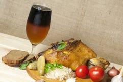 La jambe rôtie de porc a servi avec la choucroute et a coupé en tranches la bière Image libre de droits