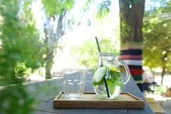 La jarra de cristal y la paja de beber y el vidrio negros tallaron el st de la taza Fotos de archivo