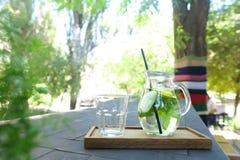 La jarra de cristal y la paja de beber y el vidrio negros tallaron el st de la taza Fotografía de archivo libre de regalías