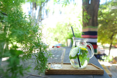 La jarra de cristal y la paja de beber y el vidrio negros tallaron el st de la taza Imagen de archivo