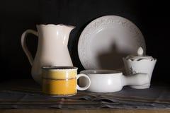La jarra oscura de la leche del estilo rural, la desnatadora y el viejo vintage asaltan en fondo negro fotografía de archivo