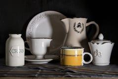 La jarra oscura de la leche del estilo rural, la desnatadora y el viejo vintage asaltan en fondo negro imagen de archivo libre de regalías