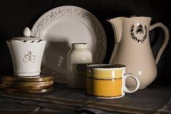 La jarra oscura de la leche del estilo rural, la desnatadora y el viejo vintage asaltan en fondo negro fotografía de archivo libre de regalías
