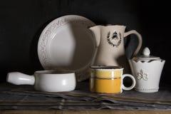 La jarra oscura de la leche del estilo rural, la desnatadora y el viejo vintage asaltan en fondo negro fotos de archivo libres de regalías