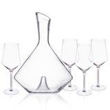 La jarra y las copas de vino cristalinas elegantes arreglaron en la superficie blanca Imagen de archivo libre de regalías