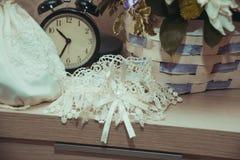 La jarretière de mariage de dentelle et le sac à main blanc de la jeune mariée sont nous la table près du réveil Photographie stock libre de droits