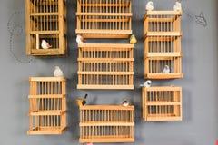 La jaula de madera del ` s del pájaro en la pared gris le gusta la decoración Imagen de archivo
