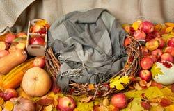 La jerarquía de ramitas con una manta en el amarillo del otoño caido se va, las manzanas, calabaza y decoración en la materia tex Imagenes de archivo