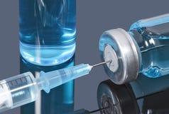 La jeringuilla con una aguja se pegó en un frasco de vacuna azul en fondo oscuro imagen de archivo