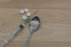 La jeringuilla y la droga y la cuchara cocinaron la heroína en un fondo de madera en el estudio foto de archivo