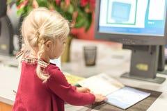 La jeune école maternelle a vieilli la fille employant le contrôle auto- au librar Photos stock