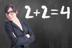 La jeune écriture de professeur de maths numérote sur le tableau photographie stock libre de droits