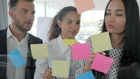 La jeune équipe d'affaires notant des idées sur les notes collantes a attaché au mur de verre, personnes de bureau observant à co banque de vidéos