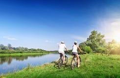 La jeune équitation de couples va à vélo dehors Photographie stock libre de droits