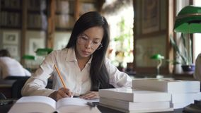 La jeune étudiante écrit se reposer à la table avec des livres dans la bibliothèque clips vidéos