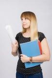 La jeune étudiante avec les dossiers et le rouleau de papier dans sa main regarde tristement de côté Photo libre de droits