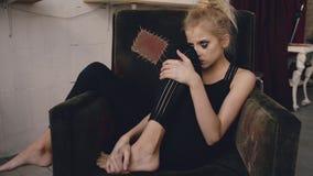 La jeune actrice d'adolescente avec le maquillage taché pleurant après le bâti de film de perte s'assied dans la chaise dans le s photos stock