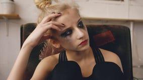 La jeune actrice d'adolescente avec le maquillage taché pleurant après le bâti de film de perte s'assied dans la chaise dans le s photographie stock libre de droits